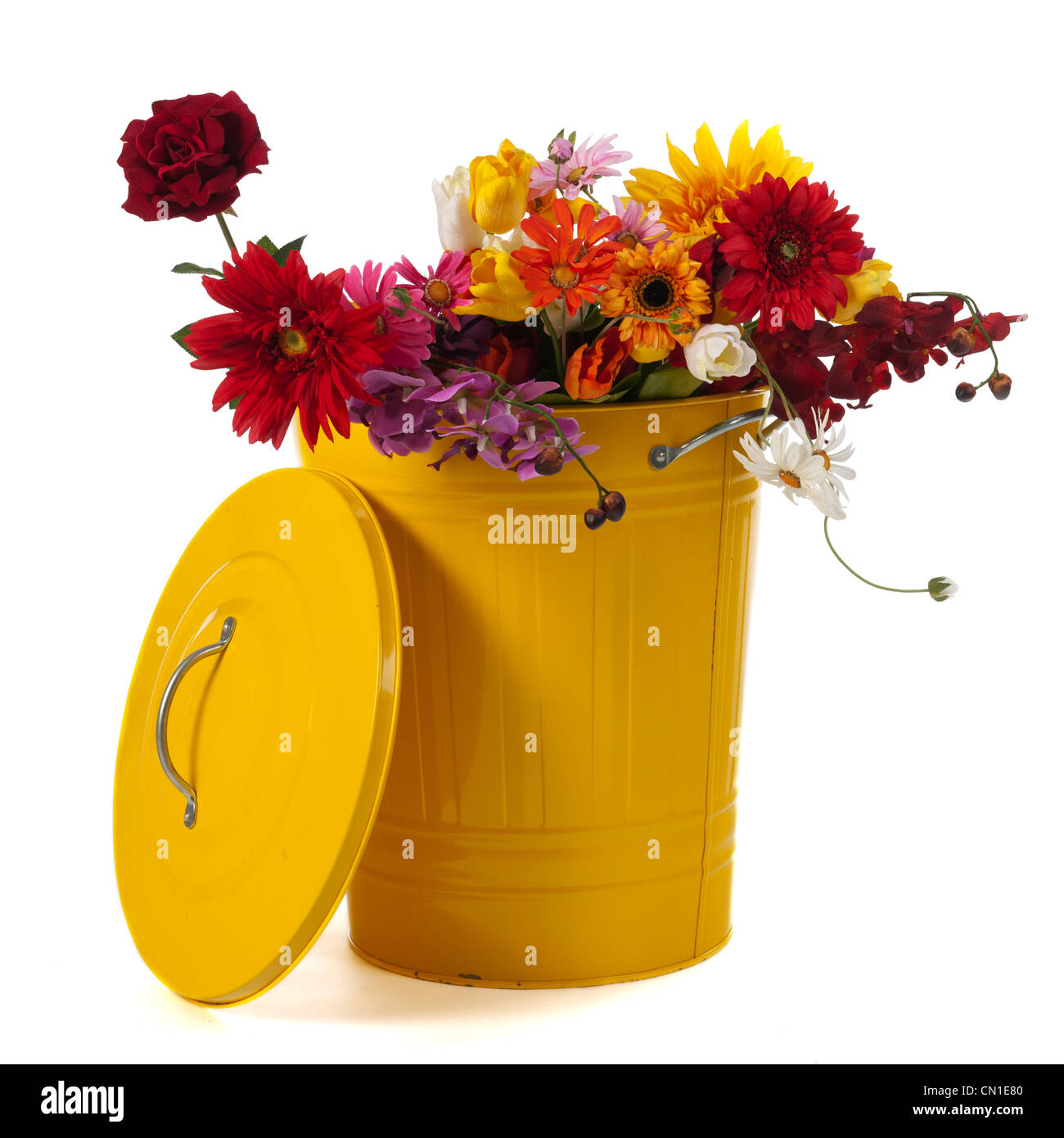 Yellow trash can filled with flowers isolated over white background Stock Photo
