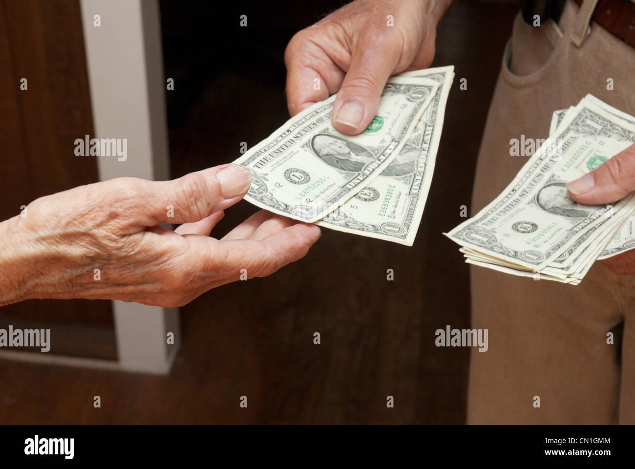 Older Man Handing Dollar Bills to Woman - Stock Image