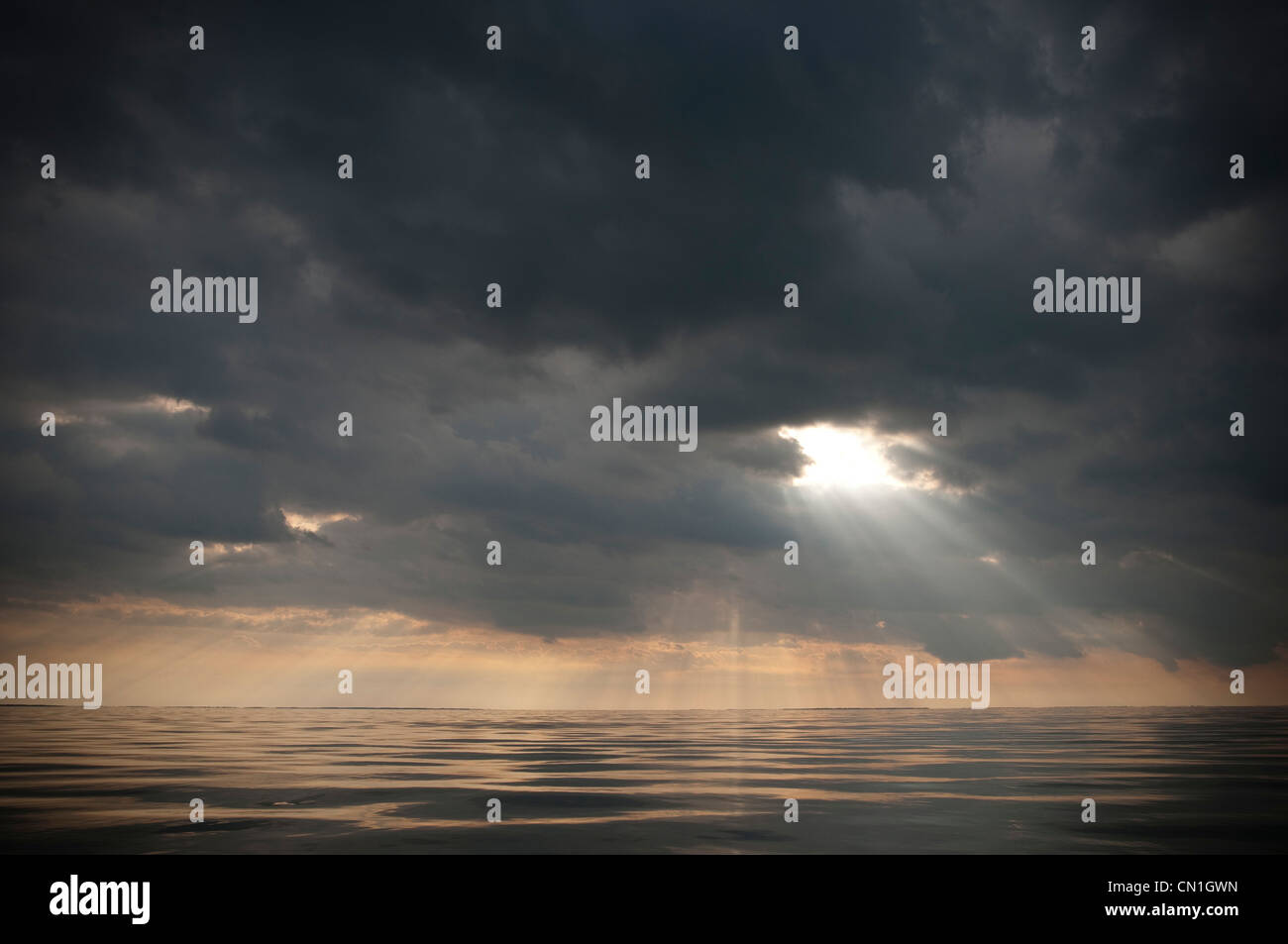 Sunlight Filtering Dramatic Gray Clouds Over Water - Stock Image