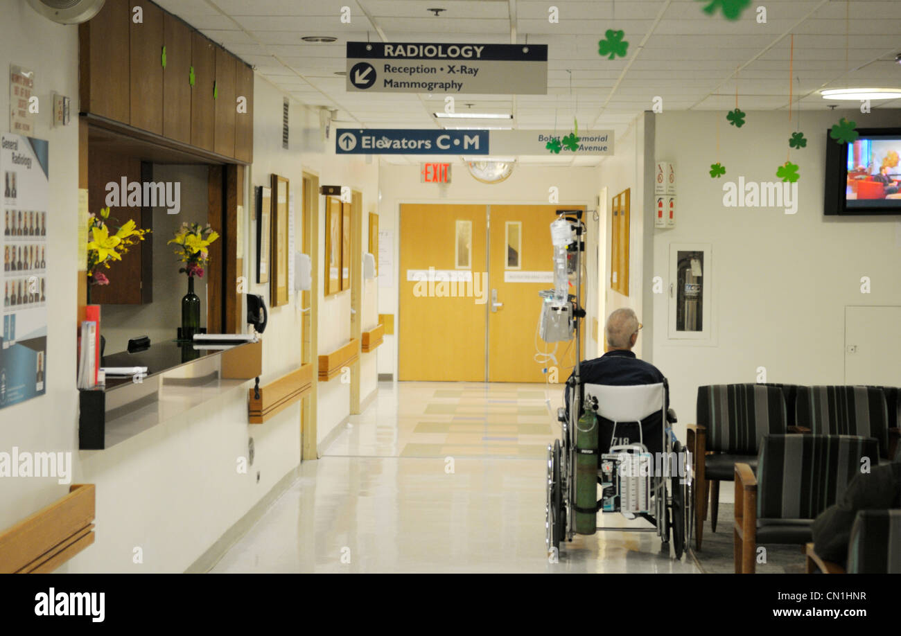 Hospital radiology waiting area with an elderly patient in a wheelchair - Stock Image