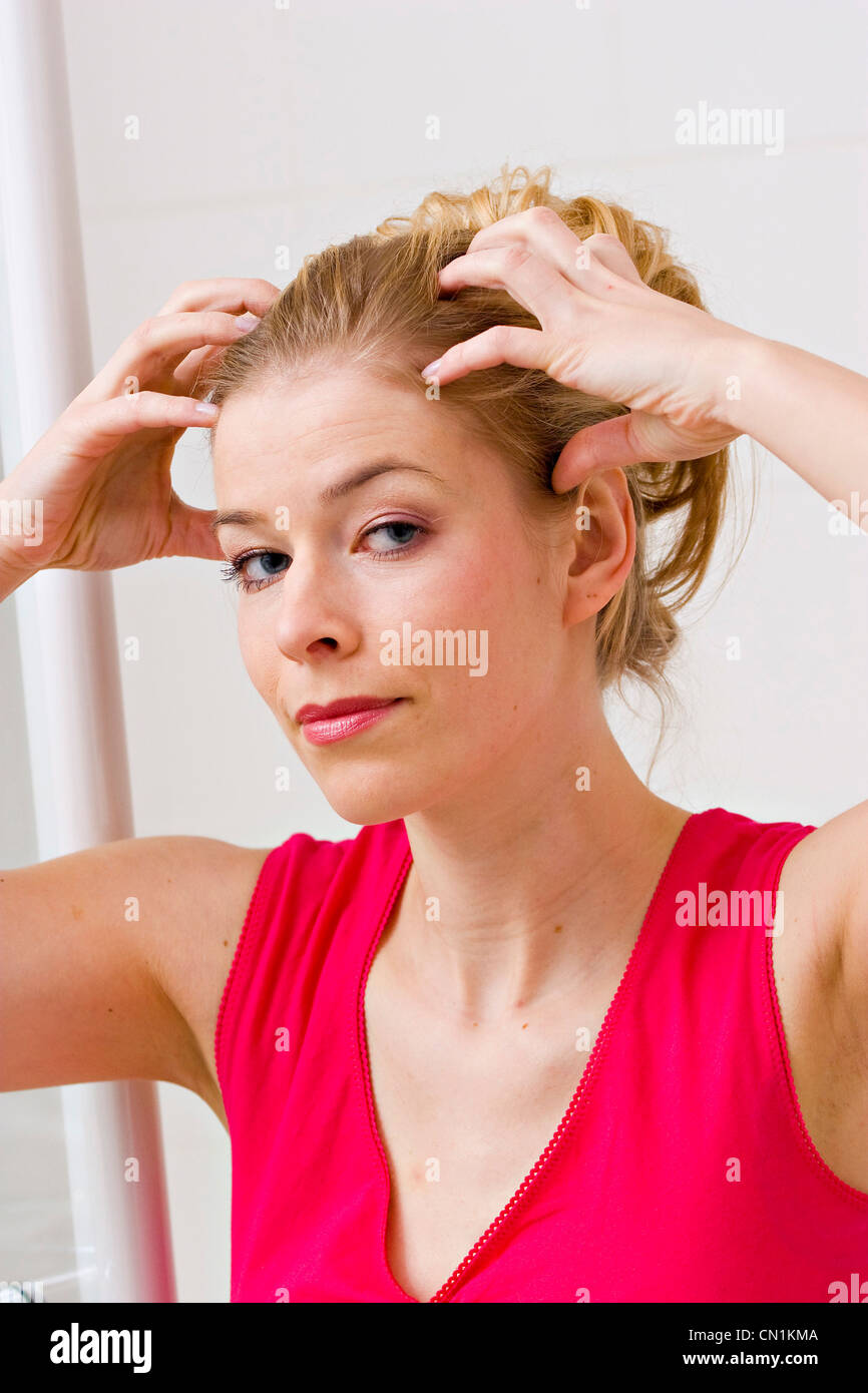 young woman massaging her head - Stock Image