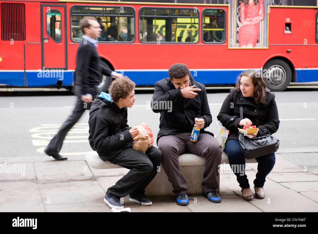 UK Oxford Street London West End young mixed race family sitting on stone bench eating fast food snack picnic red - Stock Image