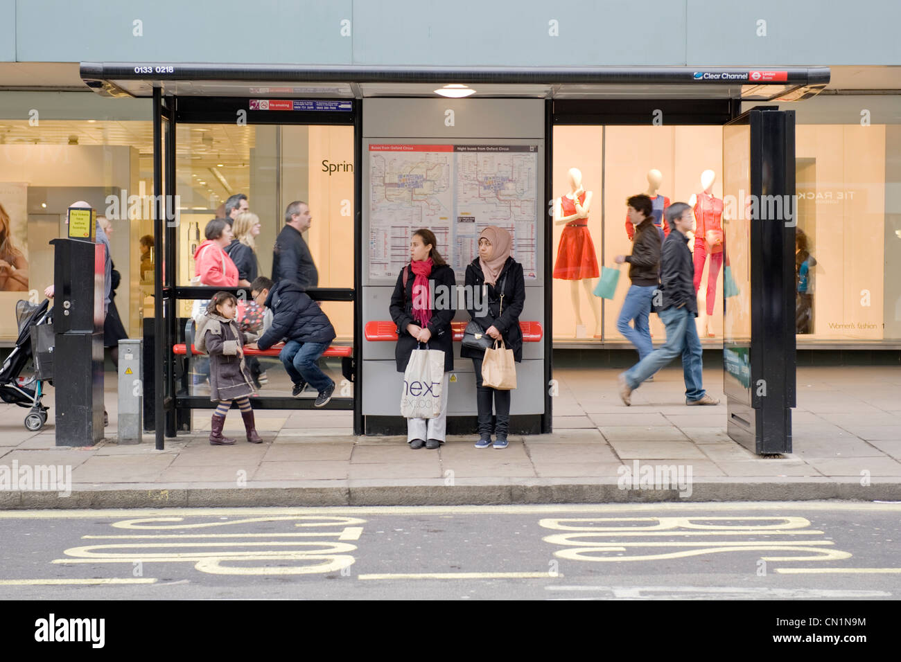 Oxford Street London West End two young ethnic girls ladies women females with children wait in bus stop shelter - Stock Image