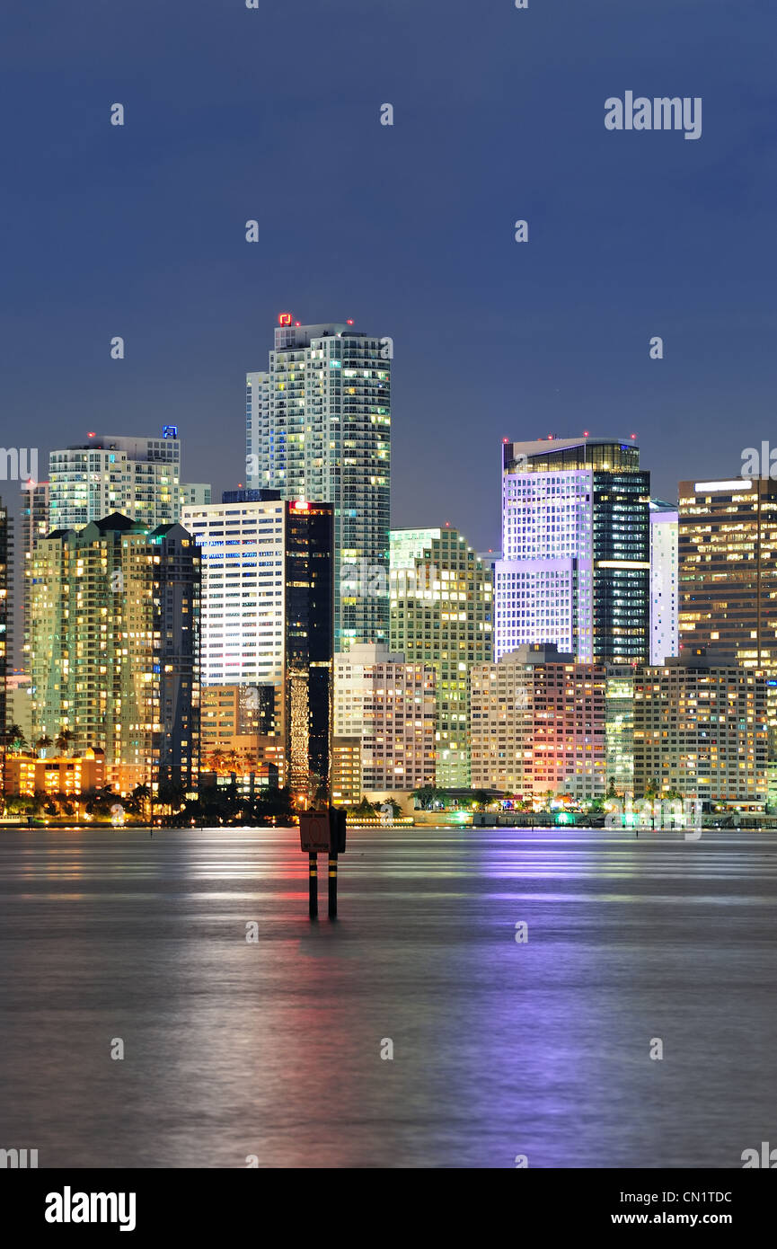 Miami city architecture closeup at dusk with urban skyscrapers over sea with reflection - Stock Image