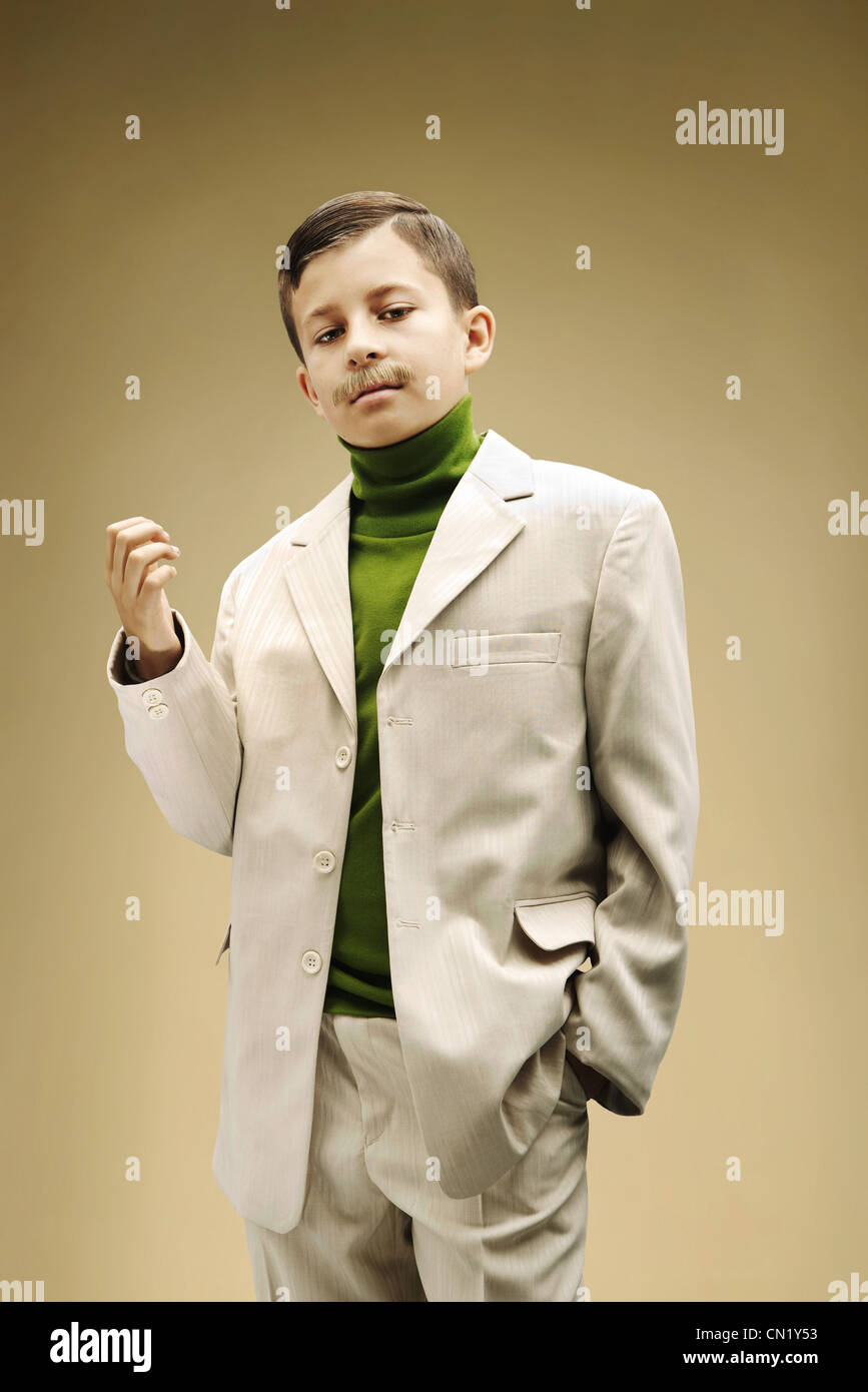 Young boy dressed in beige suit with fake mustache - Stock Image