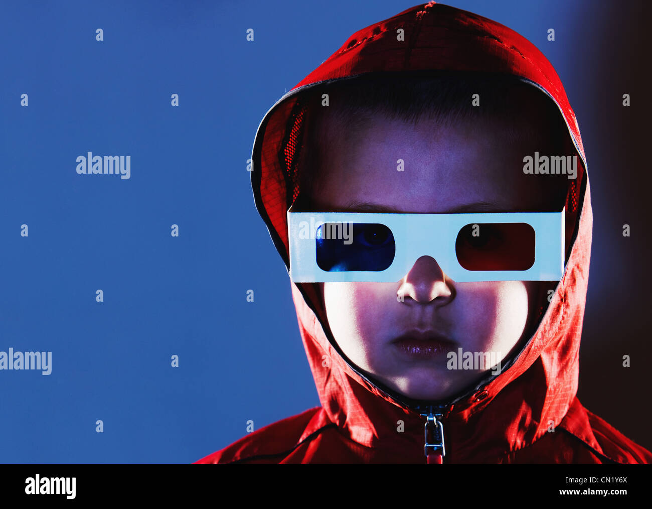 Young boy wearing 3d glasses and red hooded top - Stock Image