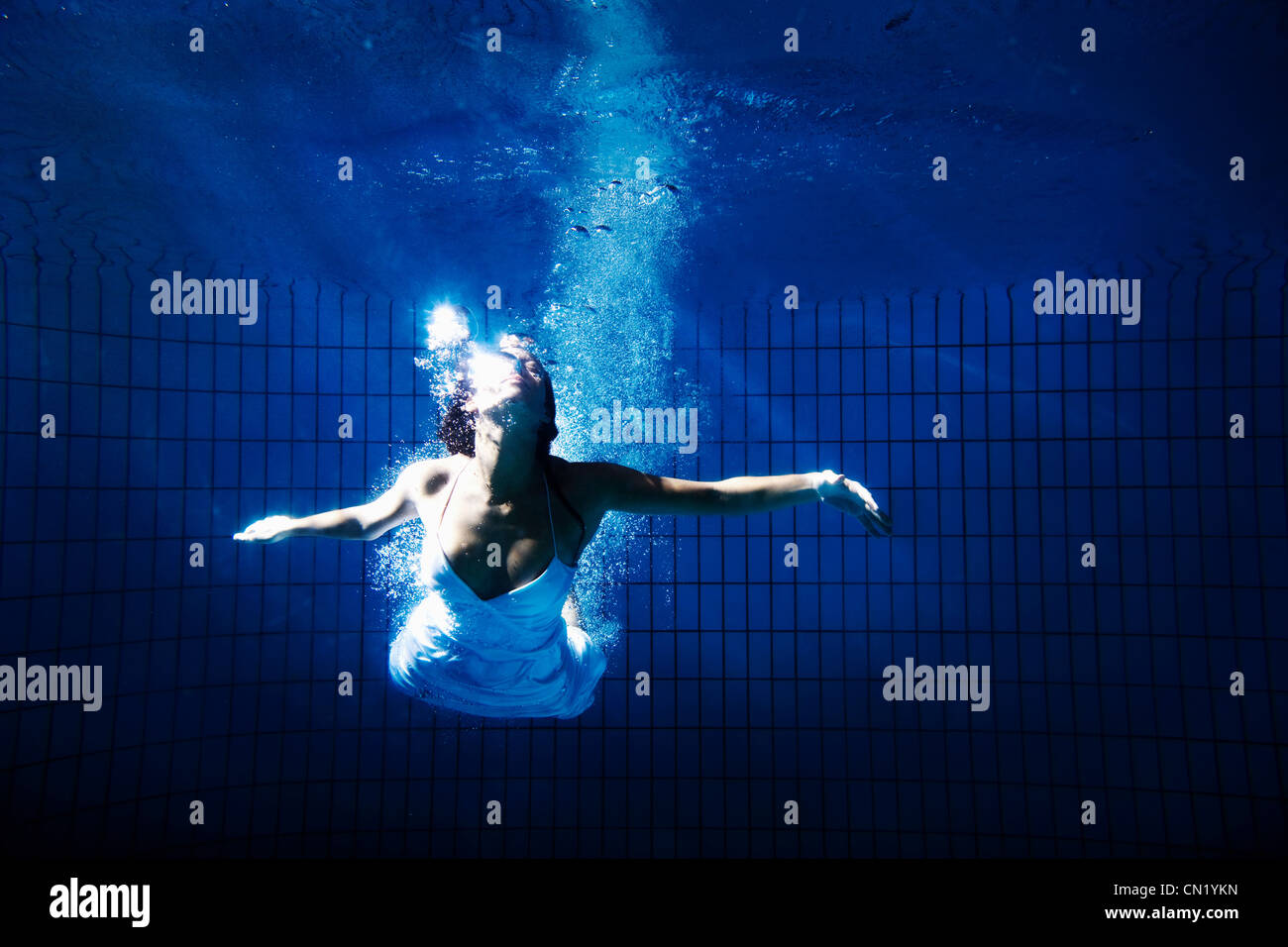 Woman in white dress underwater - Stock Image