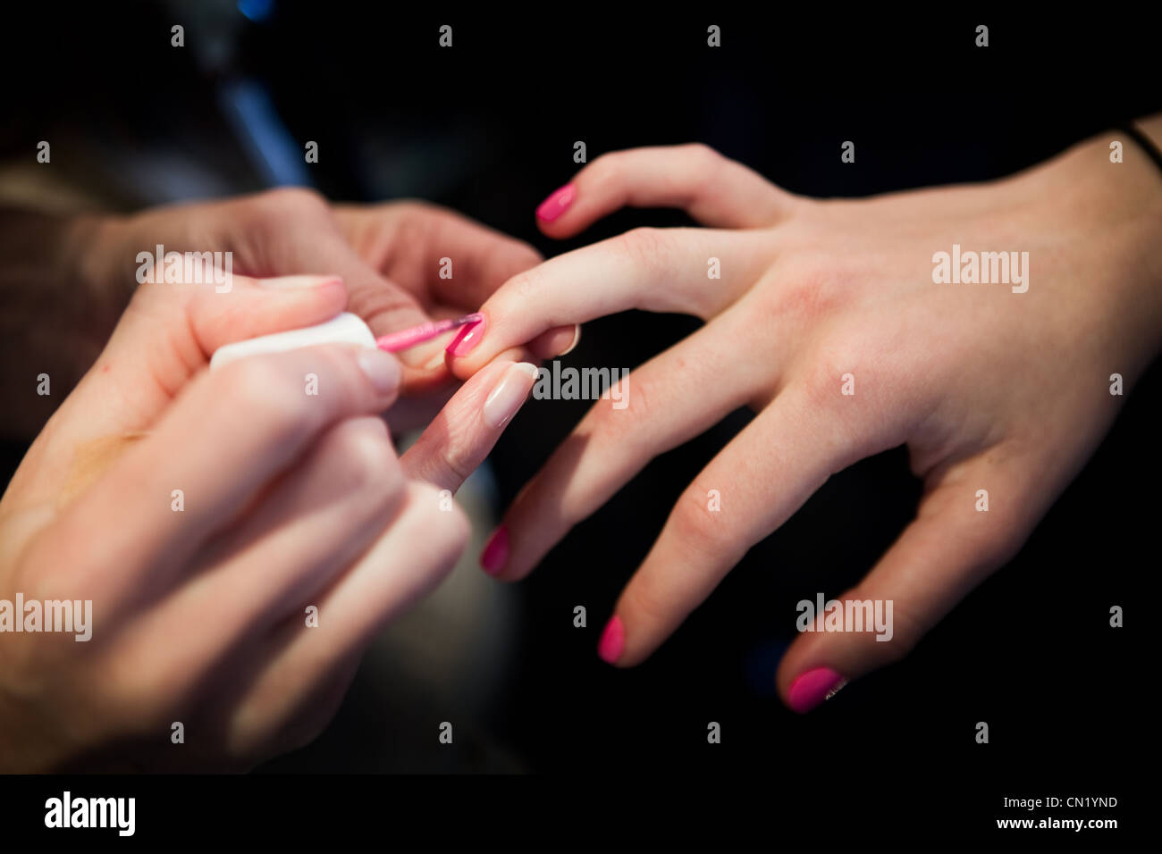 A woman having her nails painted pink - Stock Image