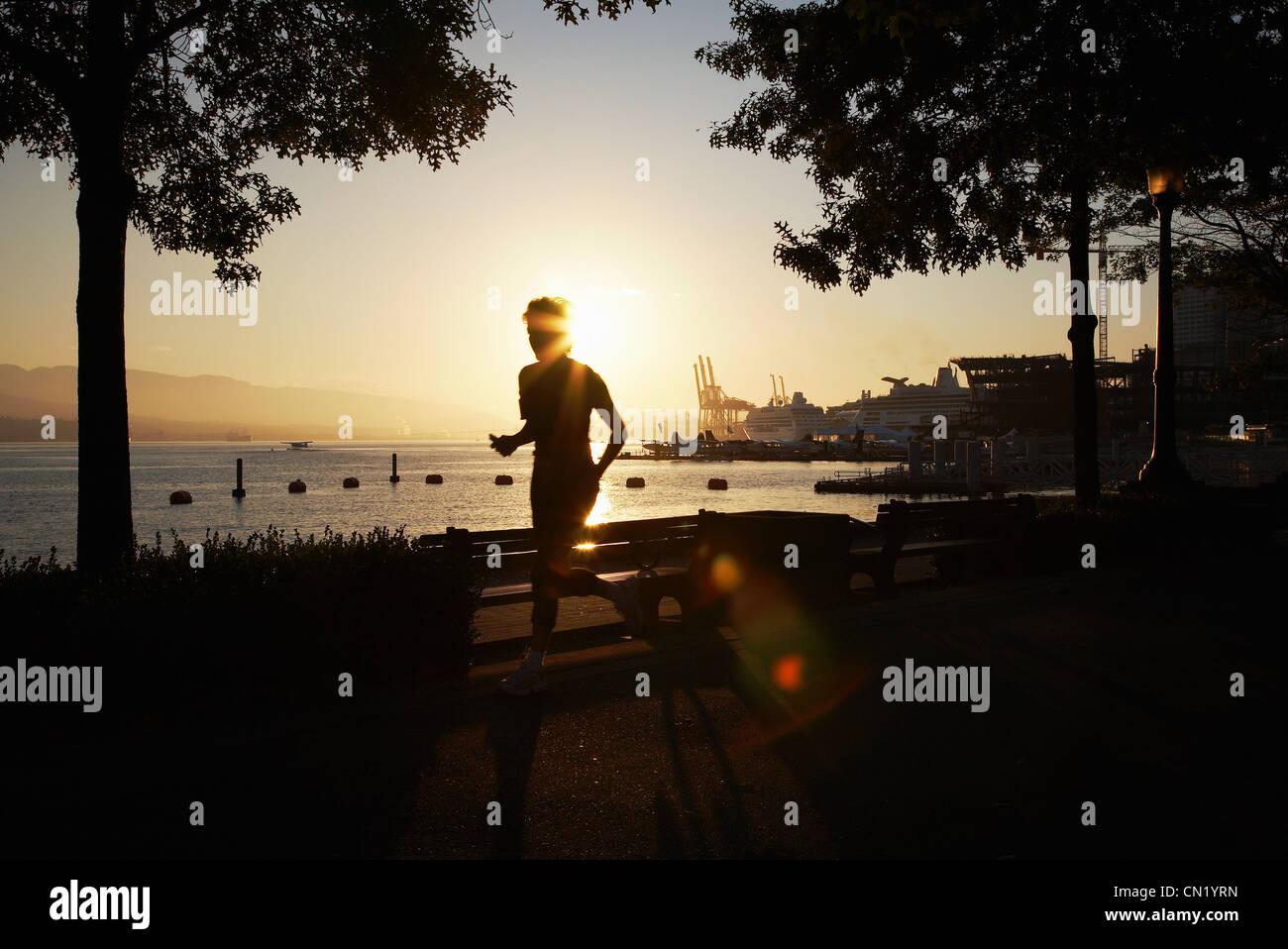Person jogging along promenade, Canada - Stock Image