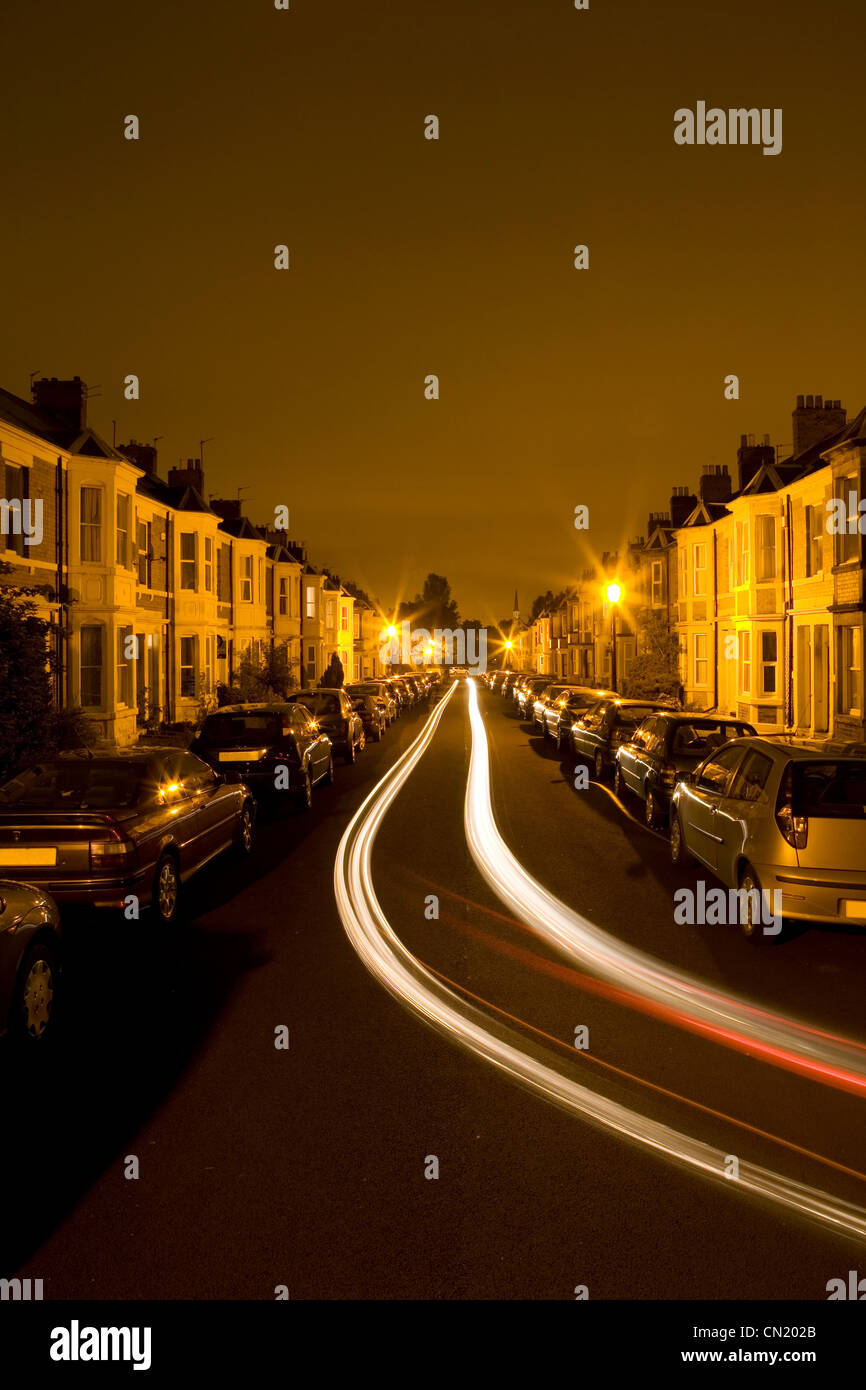 Residential street at night time with tail light of traffic - Stock Image
