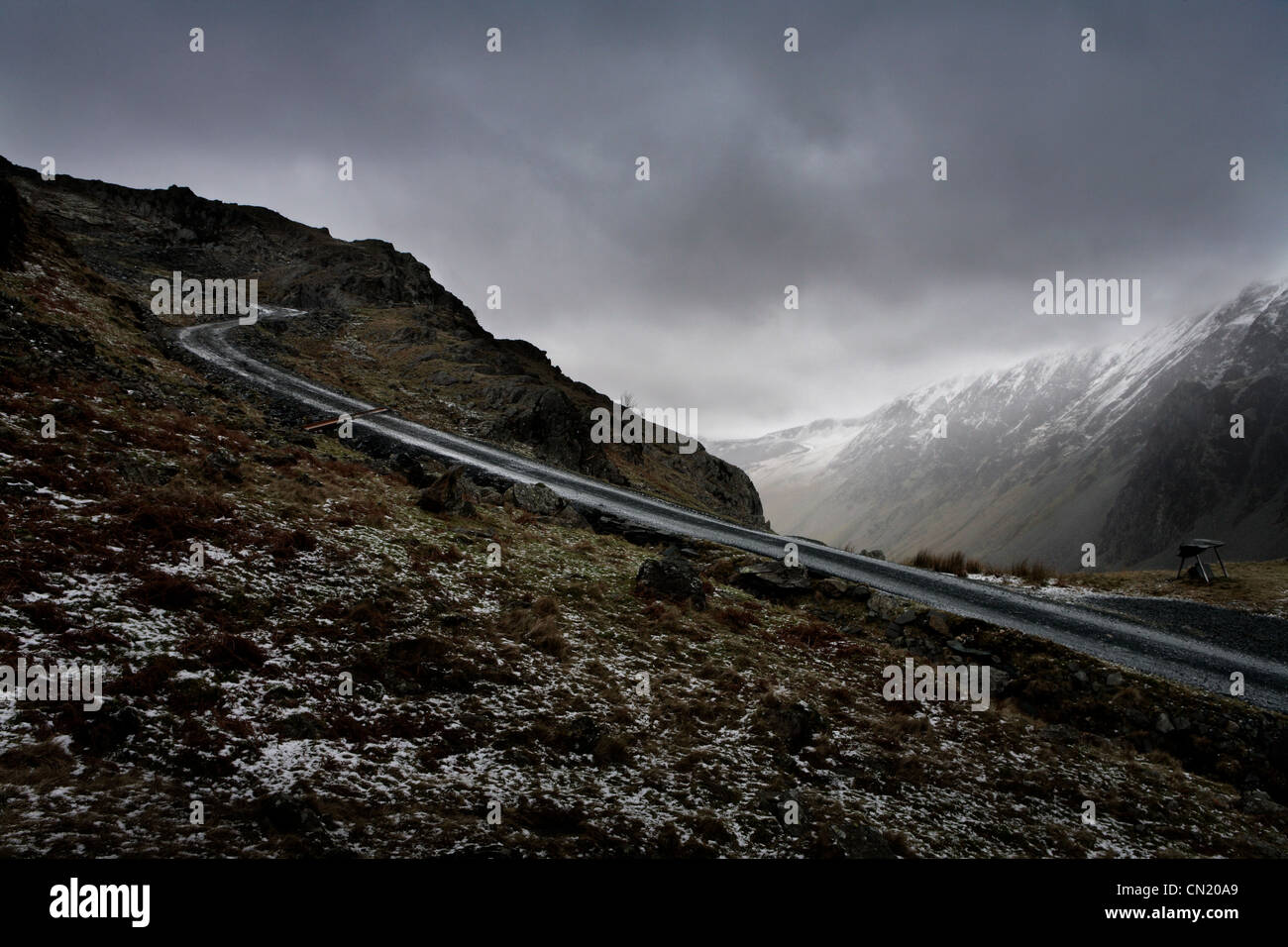 Snow and mountain road, Lake District, Cumbria, England, UK - Stock Image