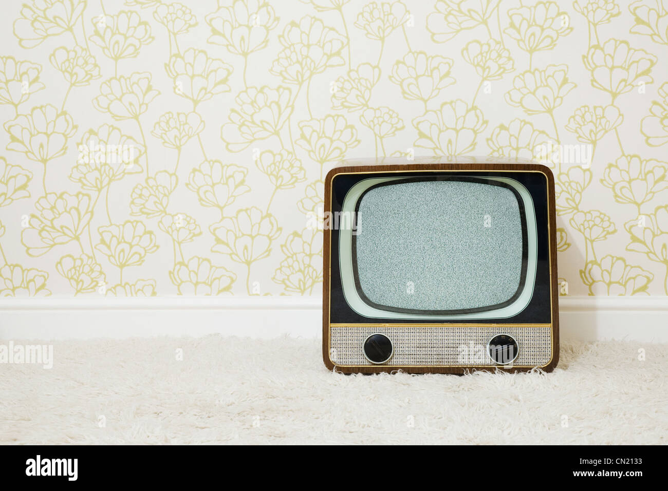 Retro television in room with patterned wallpaper Stock Photo