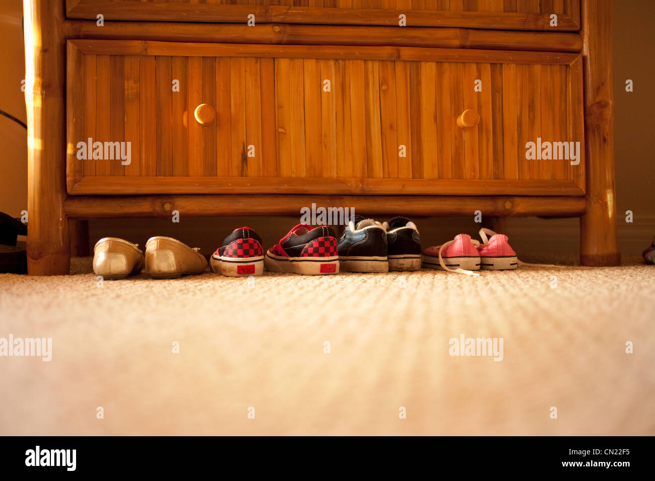 Pairs of shoes under chest of drawers - Stock Image