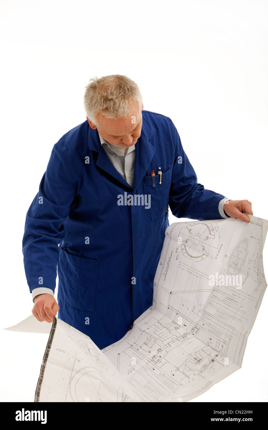 Engineer in a blue coat consulting a large open blueprint drawing engineer in a blue coat consulting a large open blueprint drawing which he is holding in his hands malvernweather Choice Image