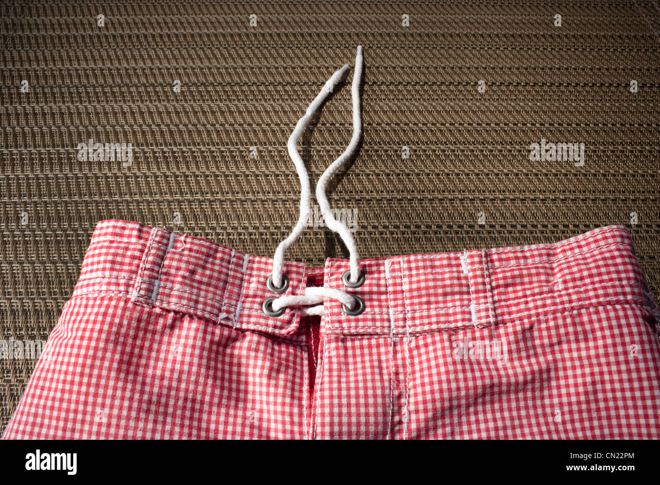 Red and white gingham swimming trunks - Stock Image
