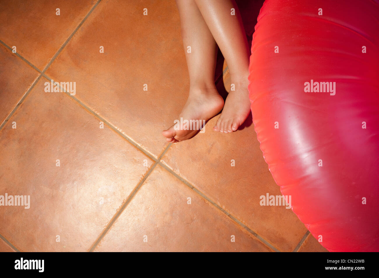 Young girl's feet and inflatable ring on tiled floor - Stock Image