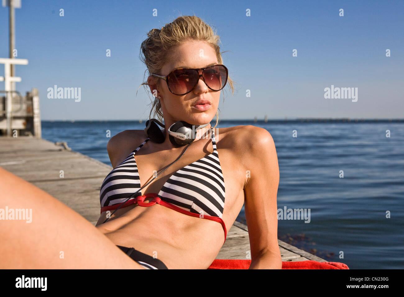 Young Woman Sunbathing on Pier - Stock Image