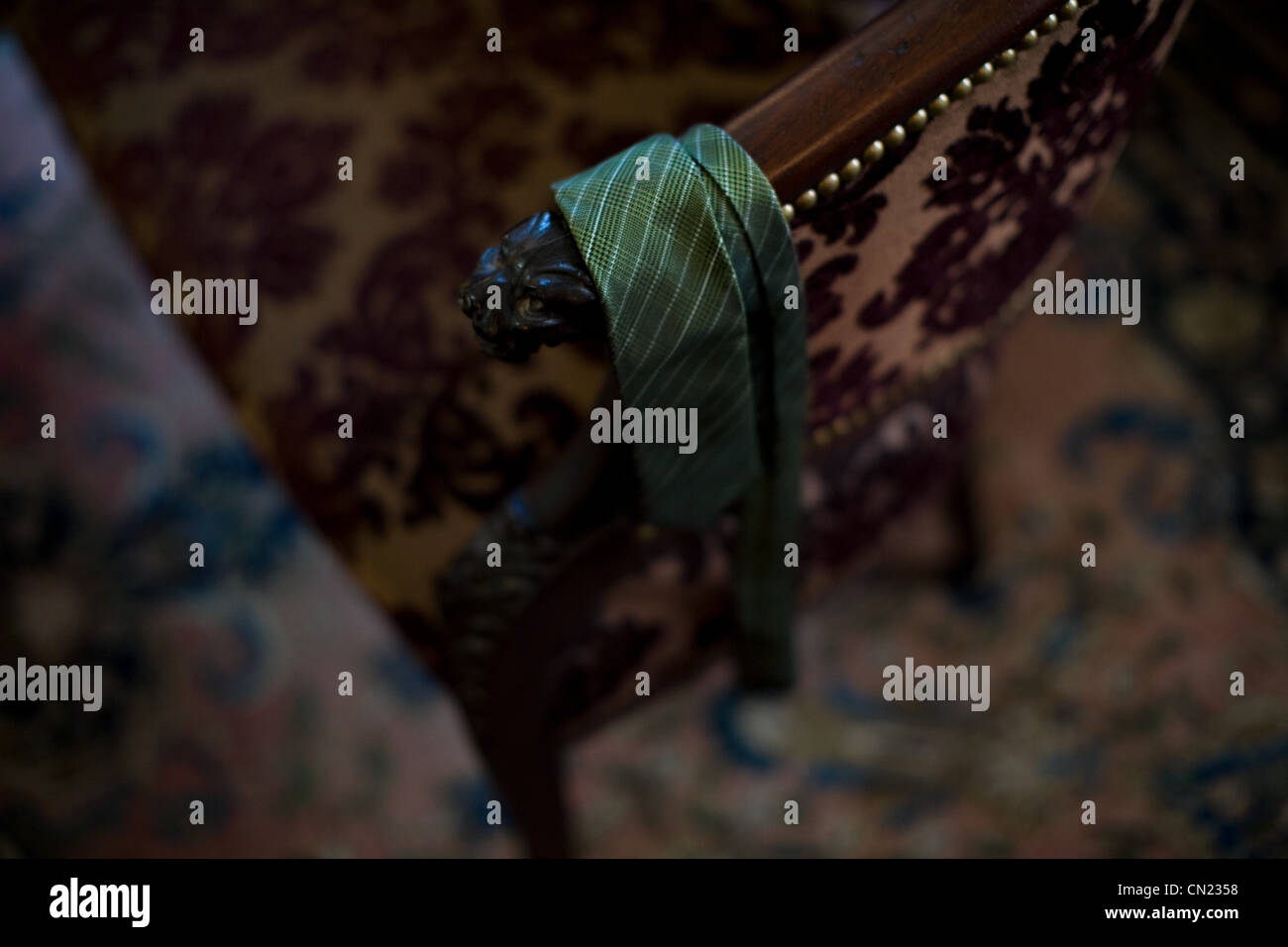 Tie draped over armchair - Stock Image