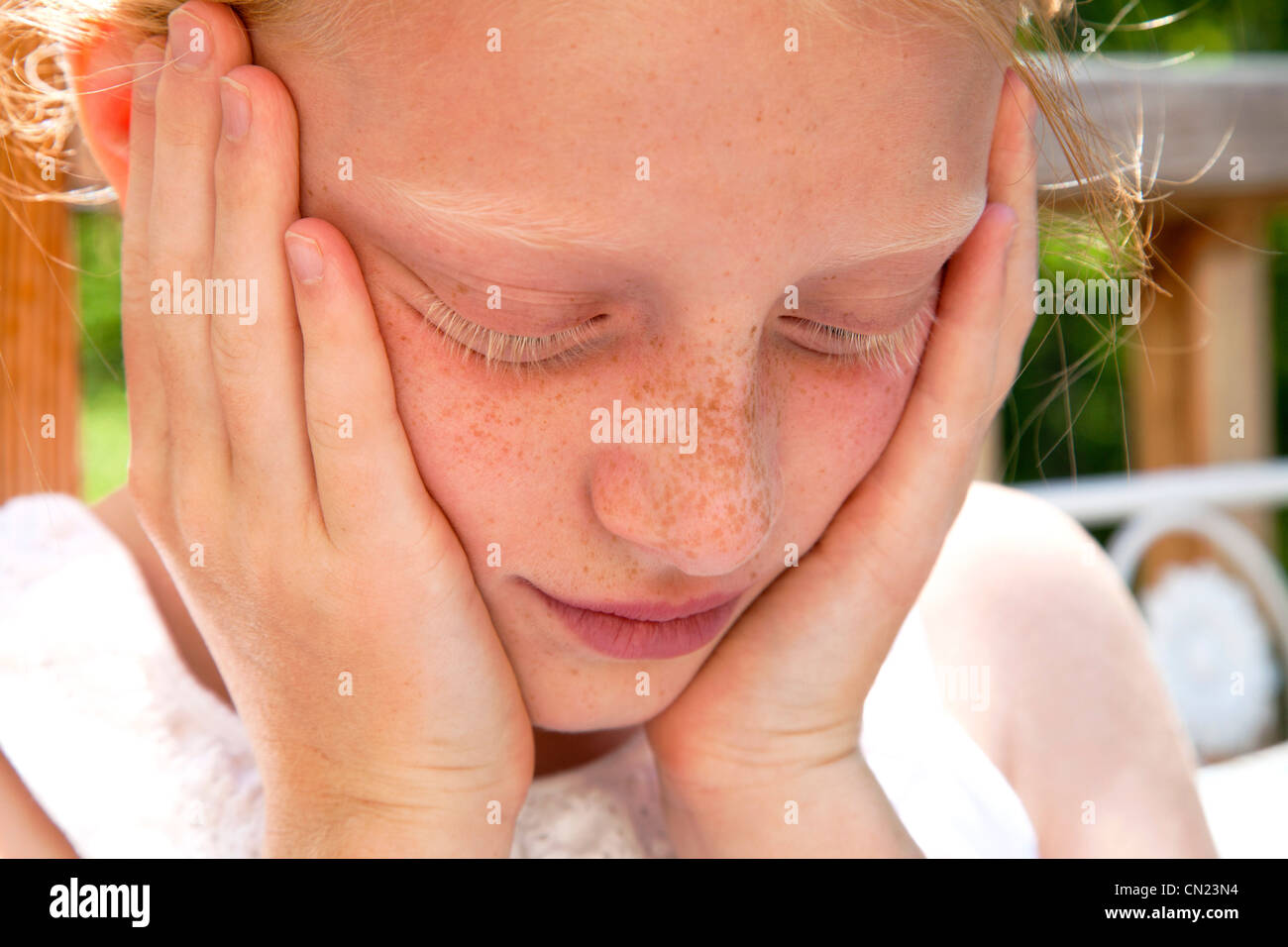 Young Freckled Girl With Hands on Face - Stock Image