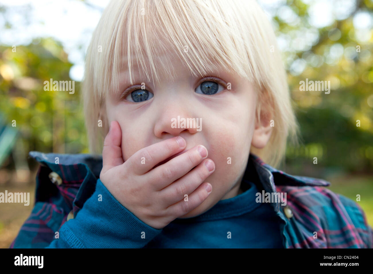 Amazed Young Blond Boy With Hand Over Mouth - Stock Image