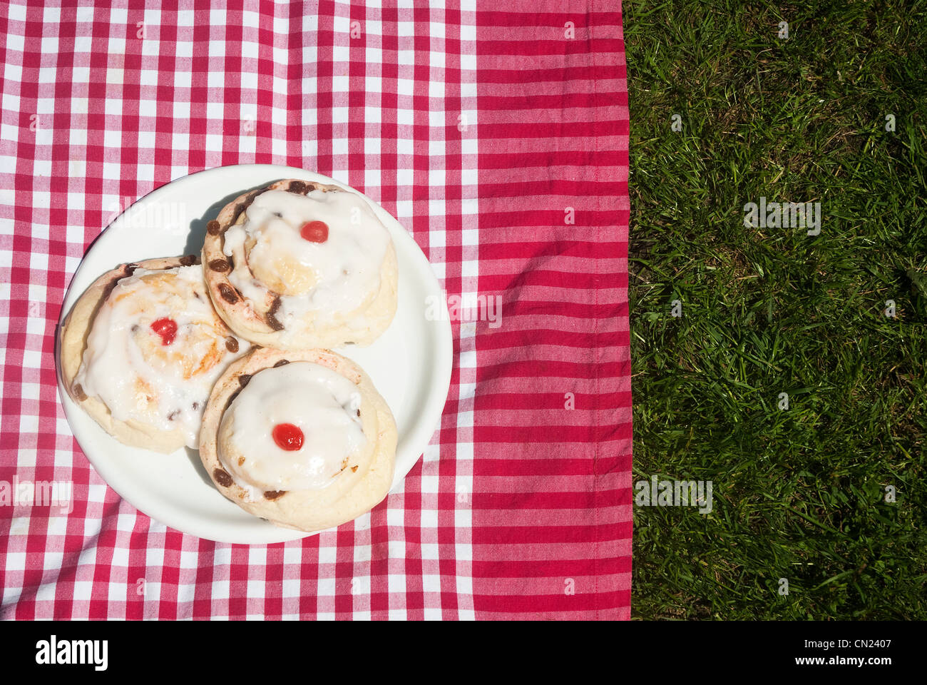 Three iced currant buns on picnic blanket - Stock Image