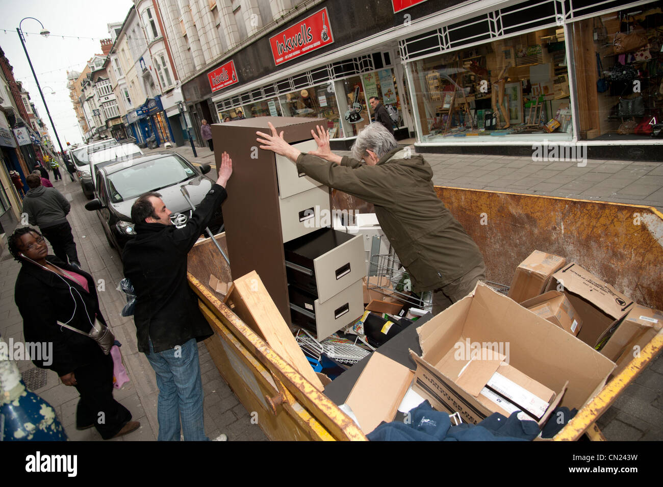 Skip raiding: People scavanging in a skip in the street for items thrown out by a shop, UK - Stock Image