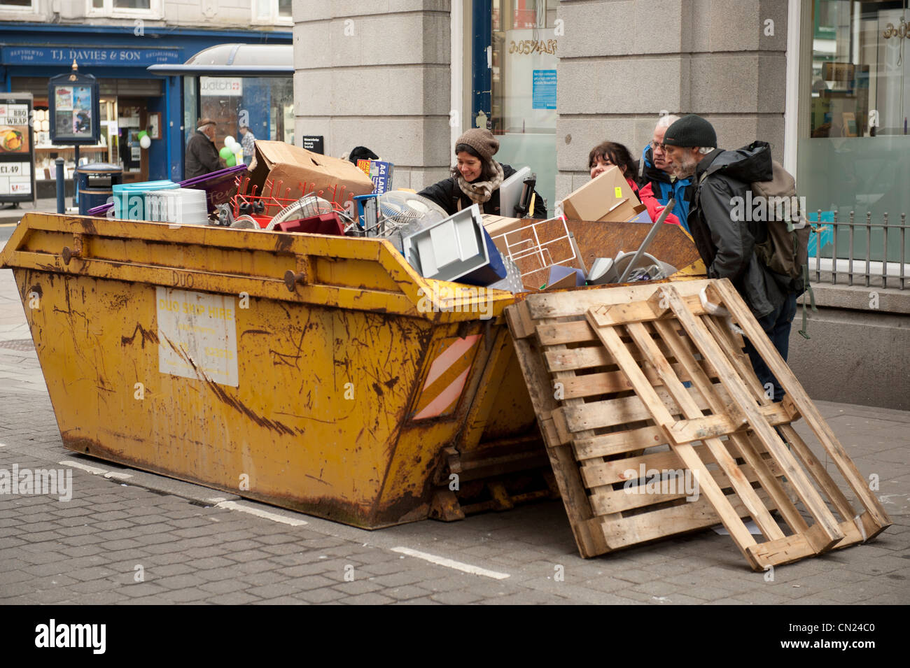 Skip raiding: People scavenging in a skip in the street for items thrown out by a shop, UK - Stock Image