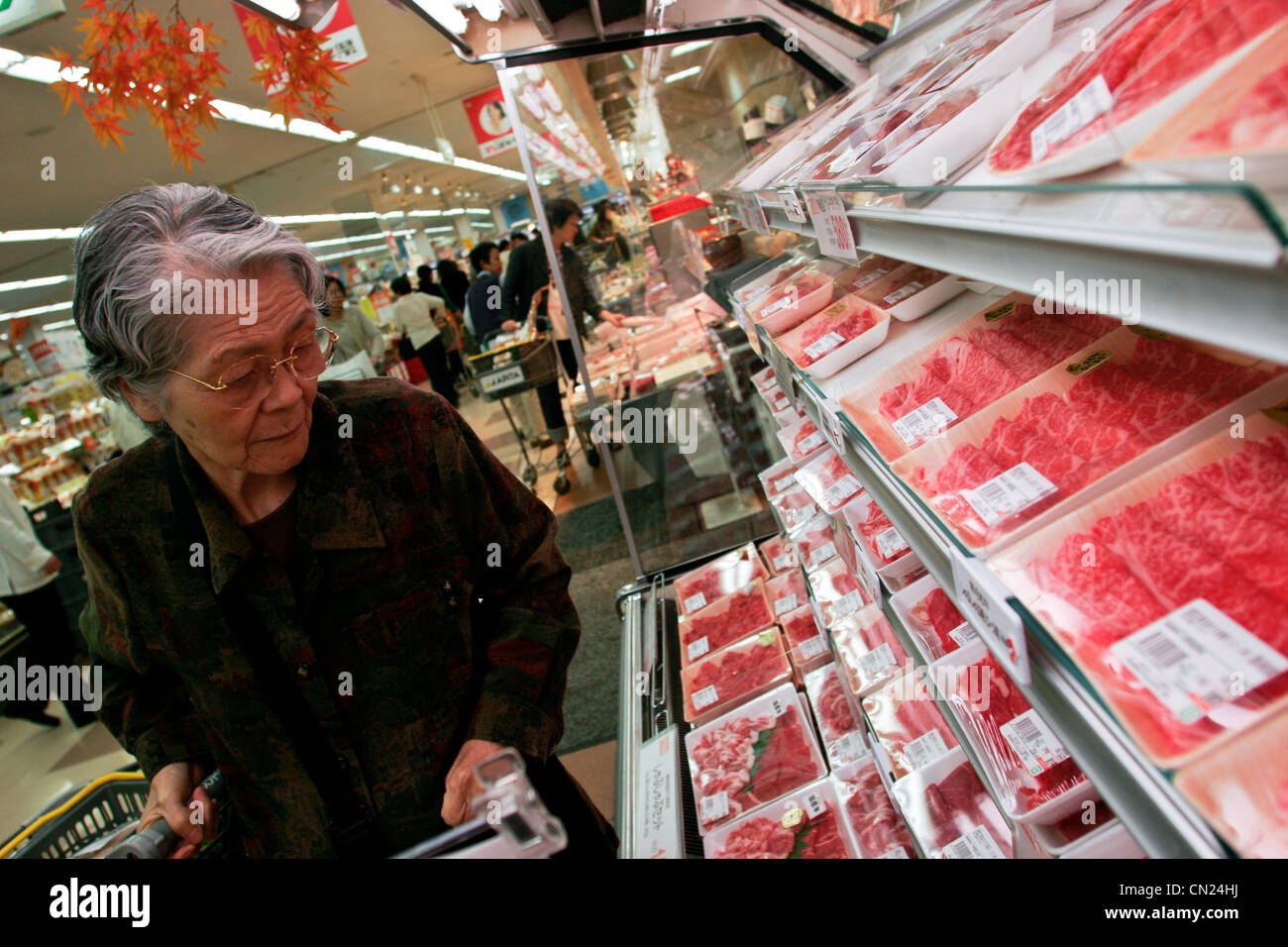 An elderly customer looks at packages of Wagyu beef at a branch of Uny Supermarket in Nagoya, Japan. - Stock Image
