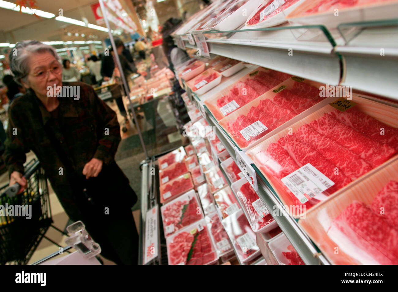 An elderly customer looks at packages of Wagyu beef at a branch of Uny Supermarket in Nagoya, Japan. Wagyu is also - Stock Image