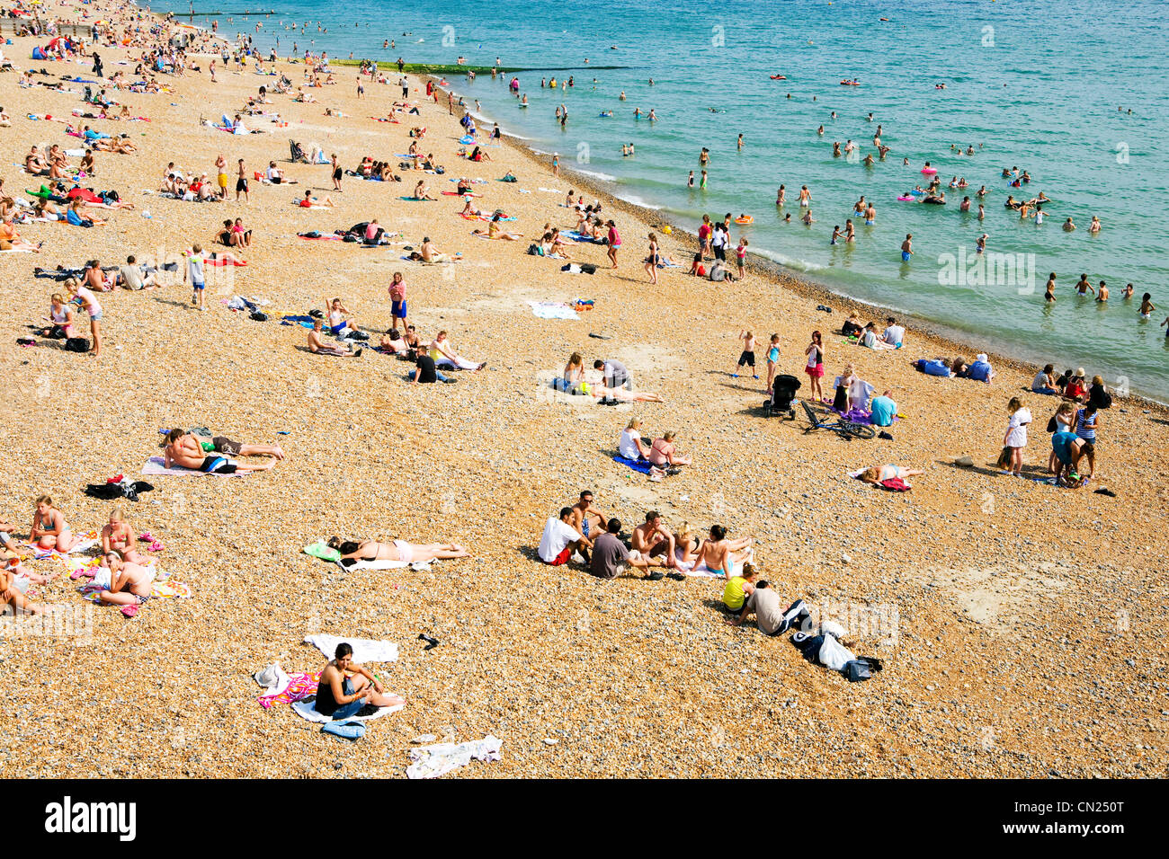 People on crowded beach, Brighton, England - Stock Image