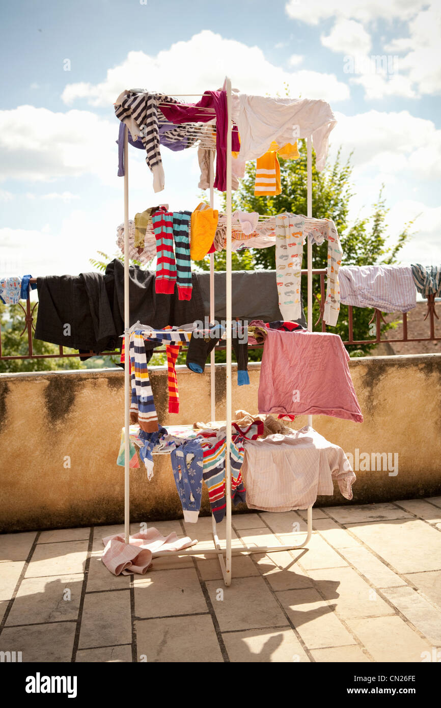 Children's clothes drying on clothes horse - Stock Image