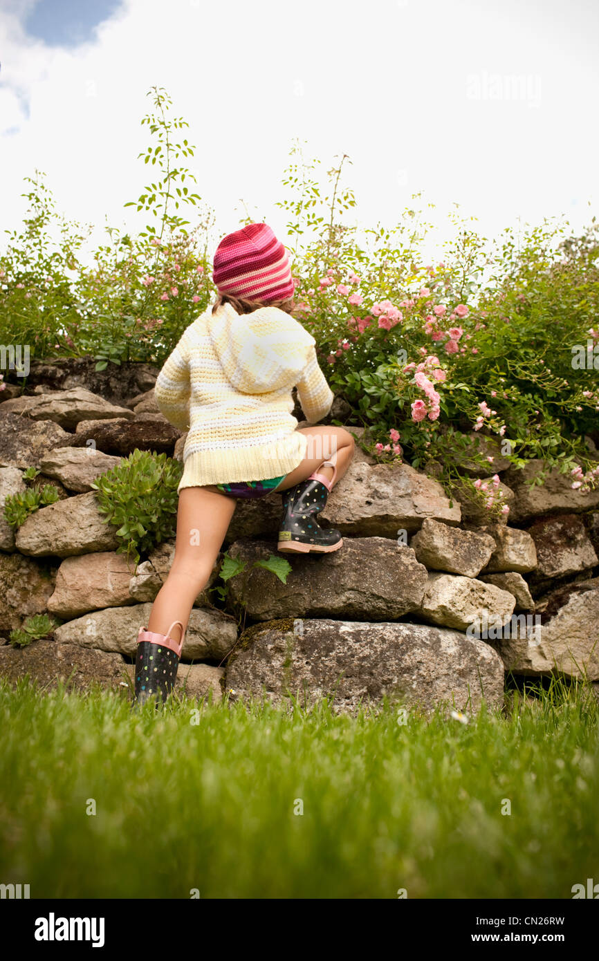Girl climbing stone wall - Stock Image