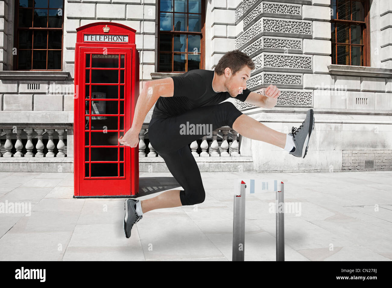 Hurdler jumping hurdle with red telephone box in background - Stock Image