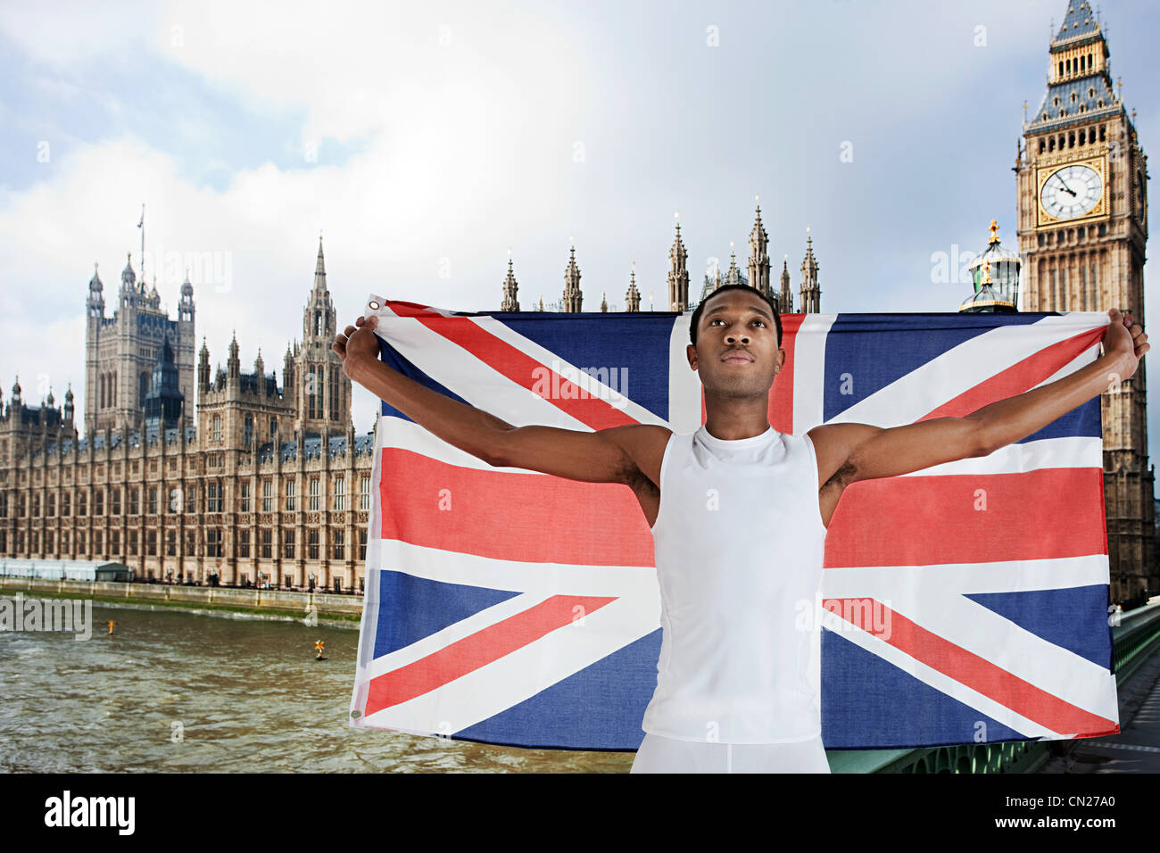 Olympic competitor with Union Jack in front of Houses of Parliament, London, England - Stock Image