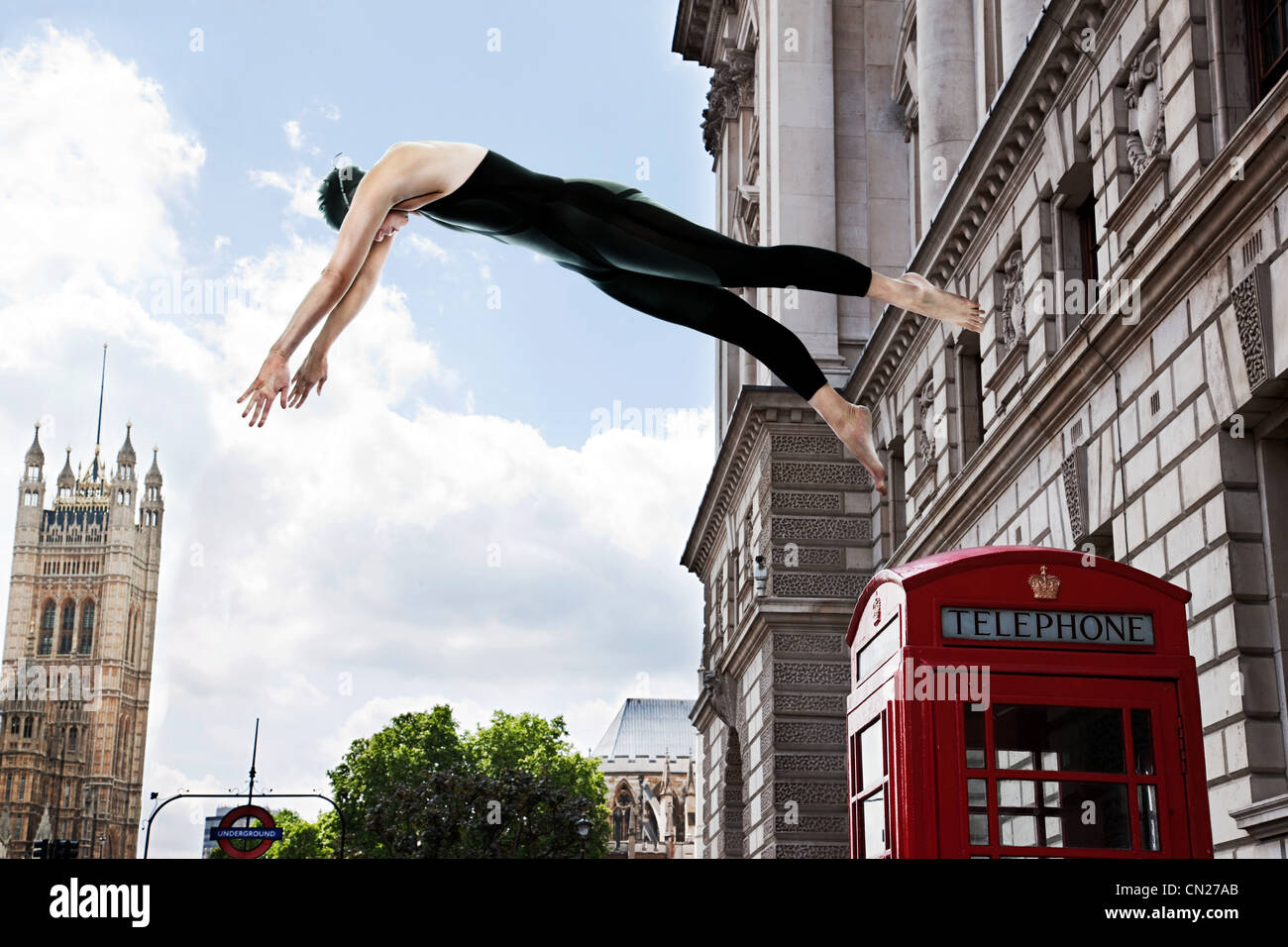 Swimmer diving from red telephone box, London, England - Stock Image