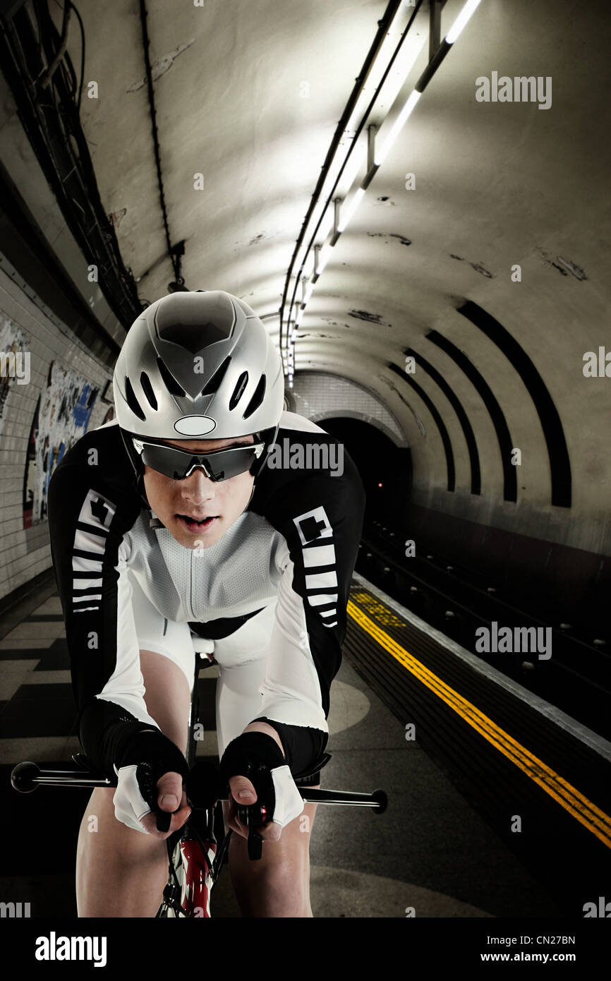Cyclist cycling in London Underground tunnel - Stock Image