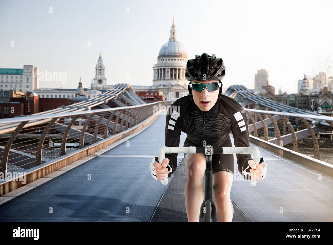 Cyclist cycling over Millennium Bridge, London, England - Stock Image