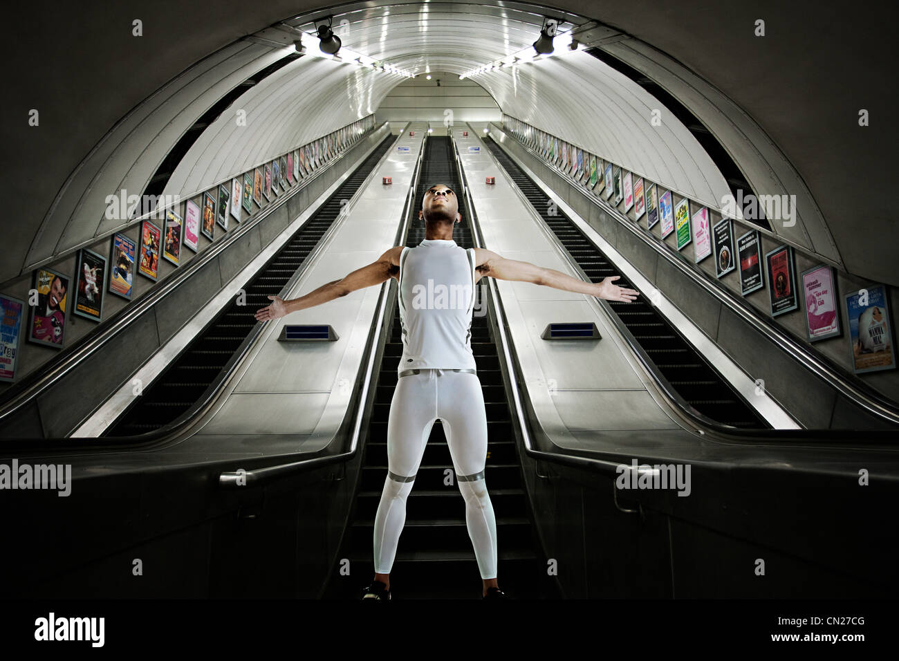 Olympic competitor standing at bottom of escalators - Stock Image