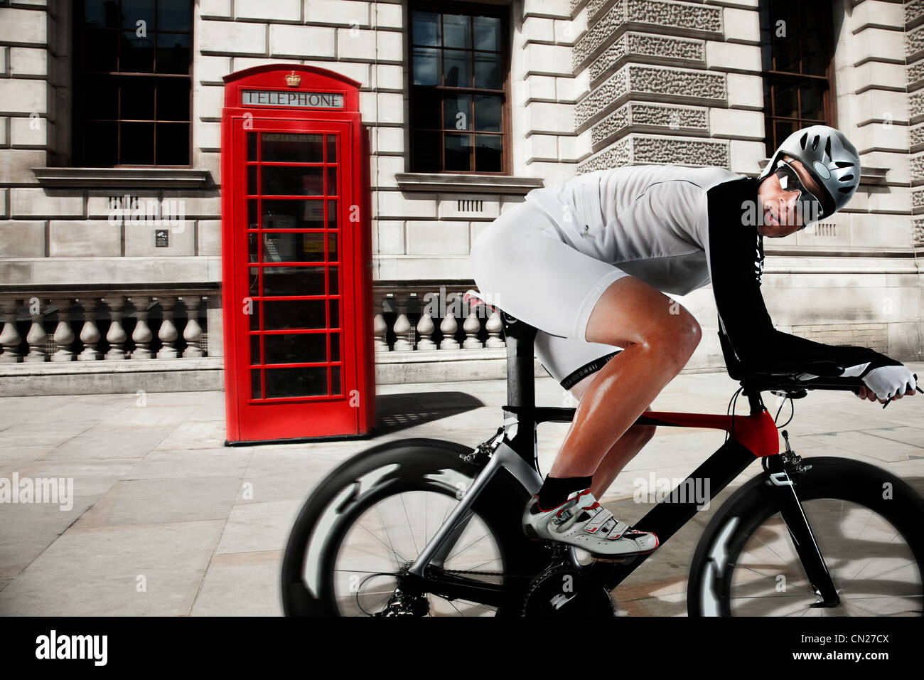 Cyclist cycling past red telephone box - Stock Image