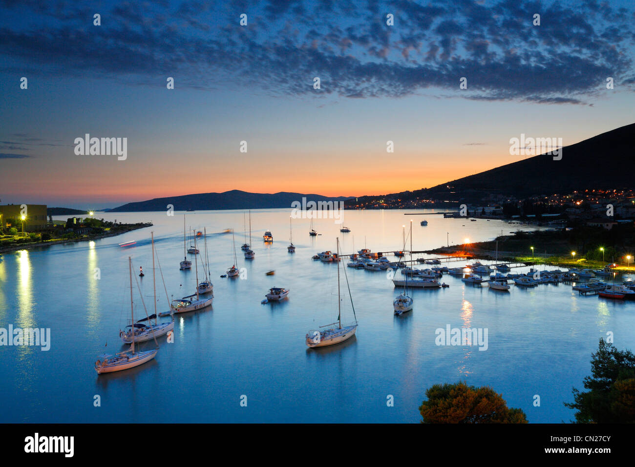 Sailboats docking by old town Trogir in Dalmatia at sunset. - Stock Image