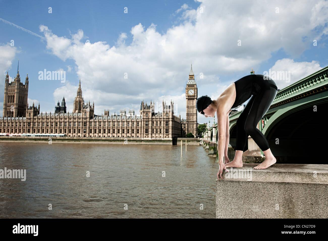 Swimmer diving off Westminster Bridge, London, England - Stock Image