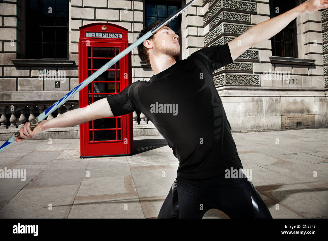 Javelin thrower with red telephone box in background - Stock Image