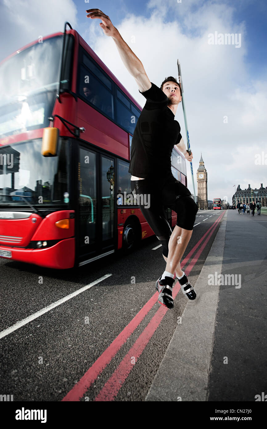 Javelin thrower on road with bus, London, England - Stock Image