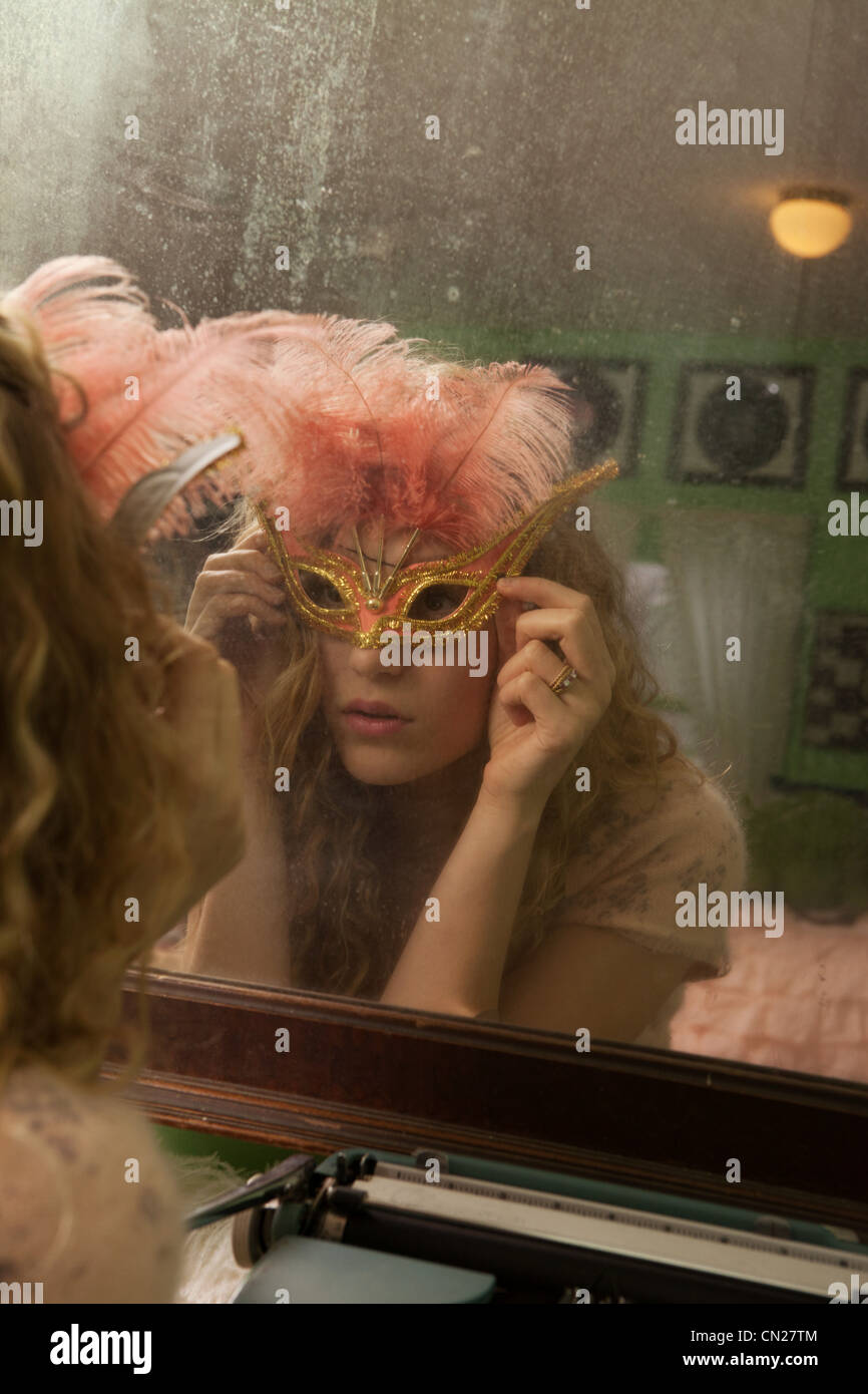 Teenage girl wearing masquerade mask in front of mirror Stock Photo