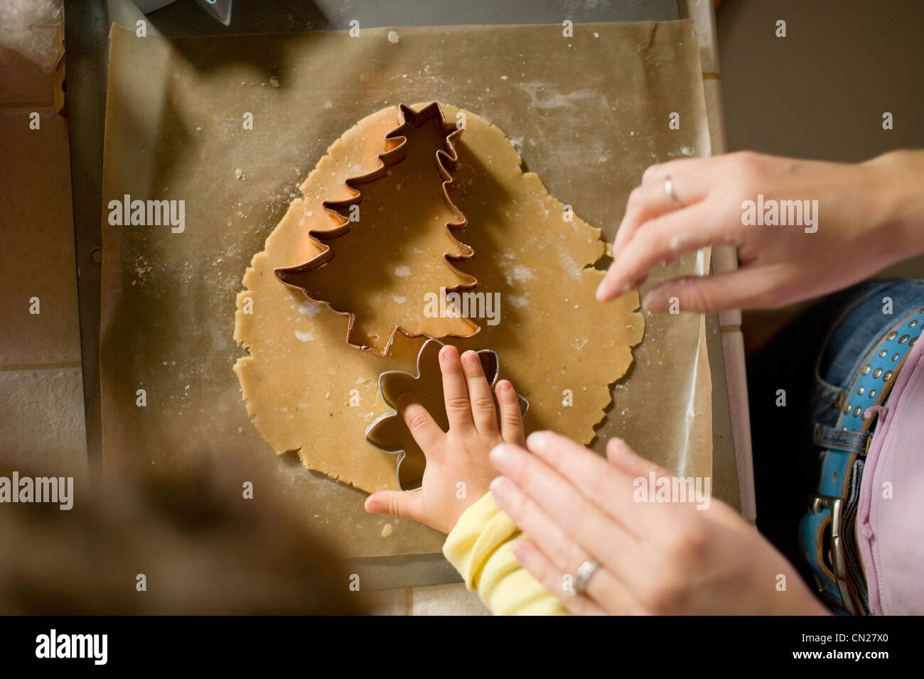 Mother and daughter cutting dough with cookie cutters - Stock Image