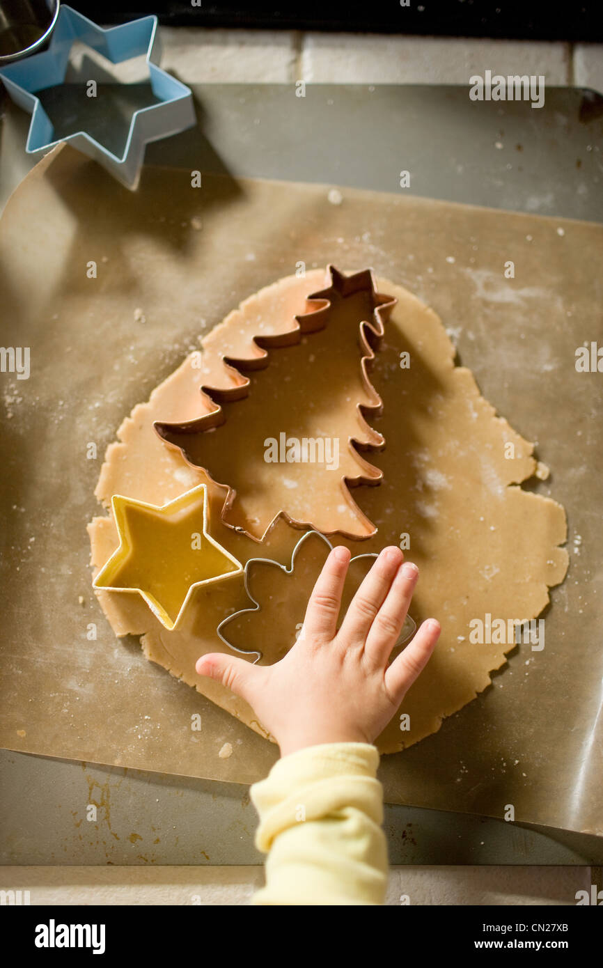Girl cutting dough with cookie cutters - Stock Image
