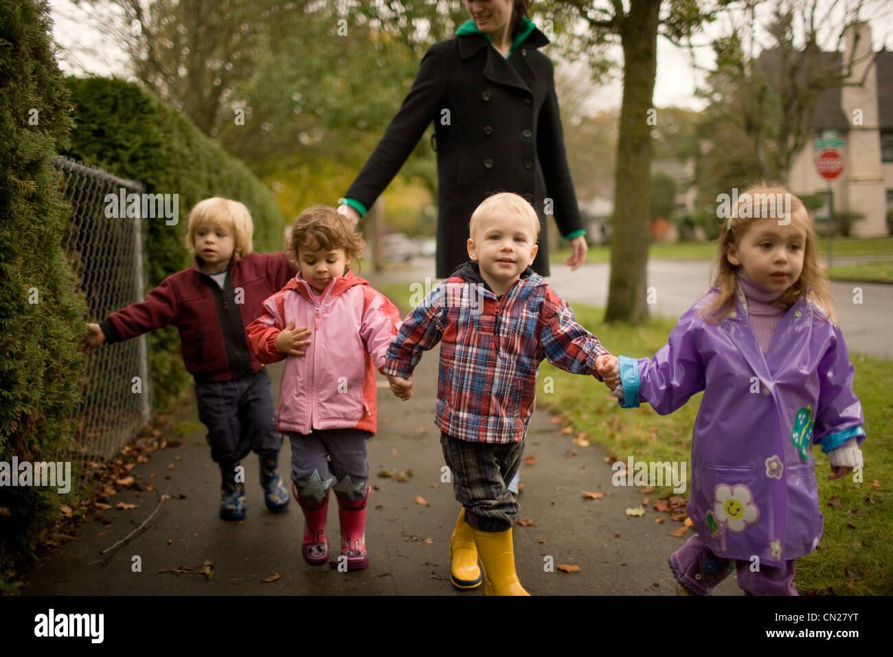Woman with four children walking along pavement Stock Photo