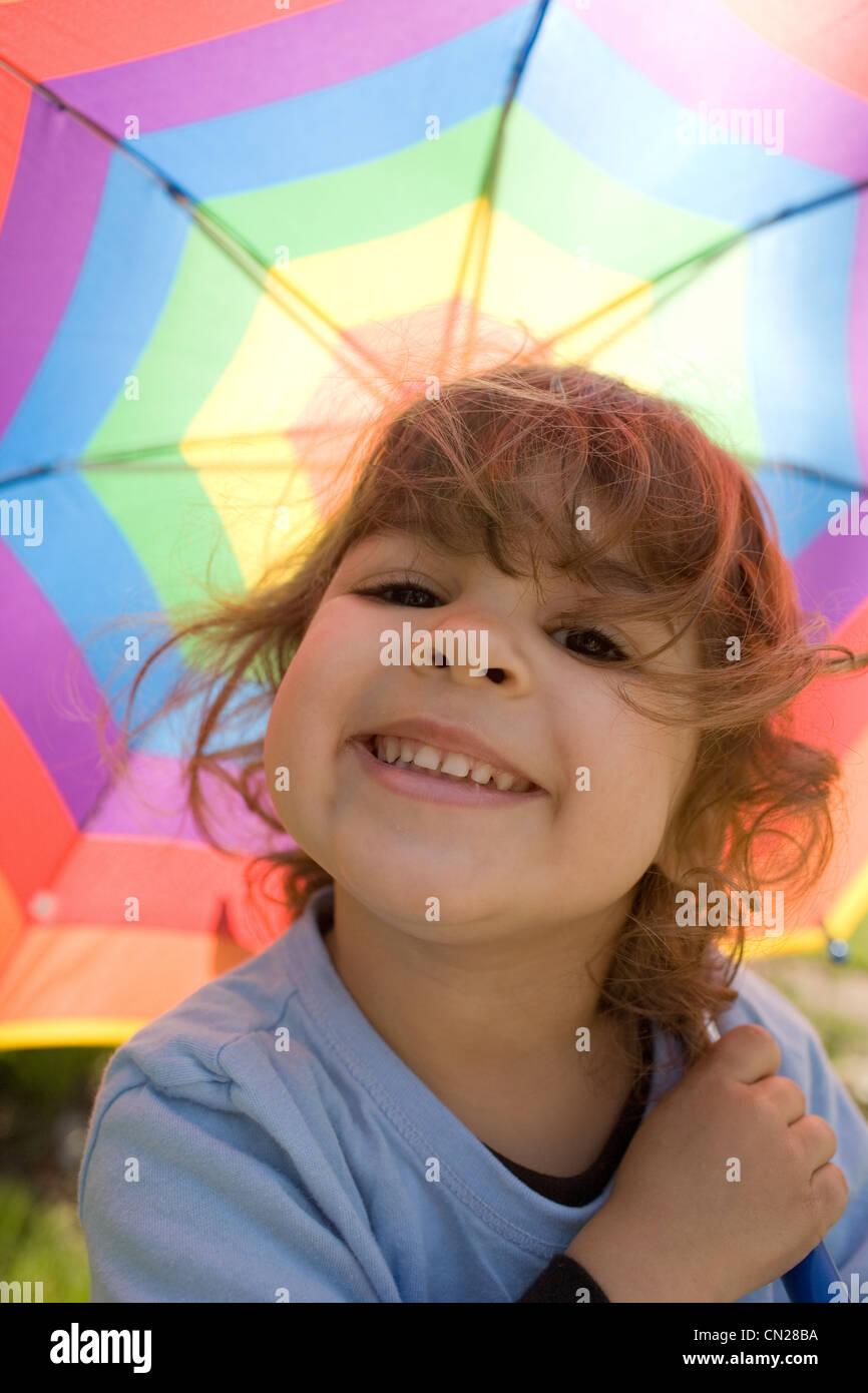 Young girl under multicolored umbrella - Stock Image