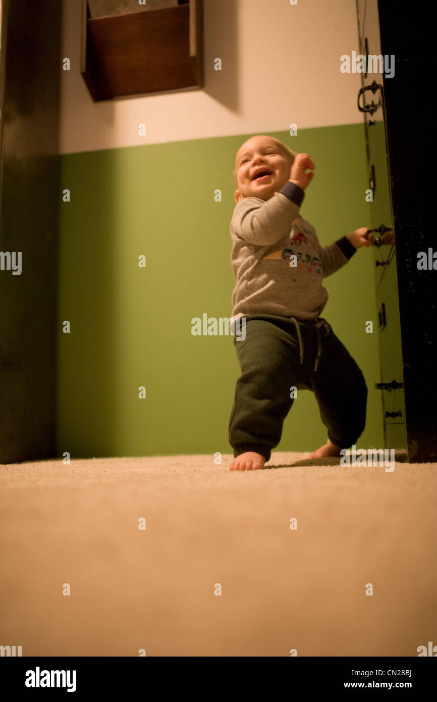 Toddler boy taking first steps - Stock Image