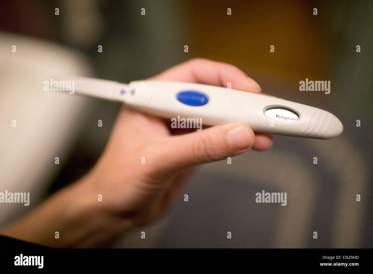 Woman holding pregnancy test - Stock Image